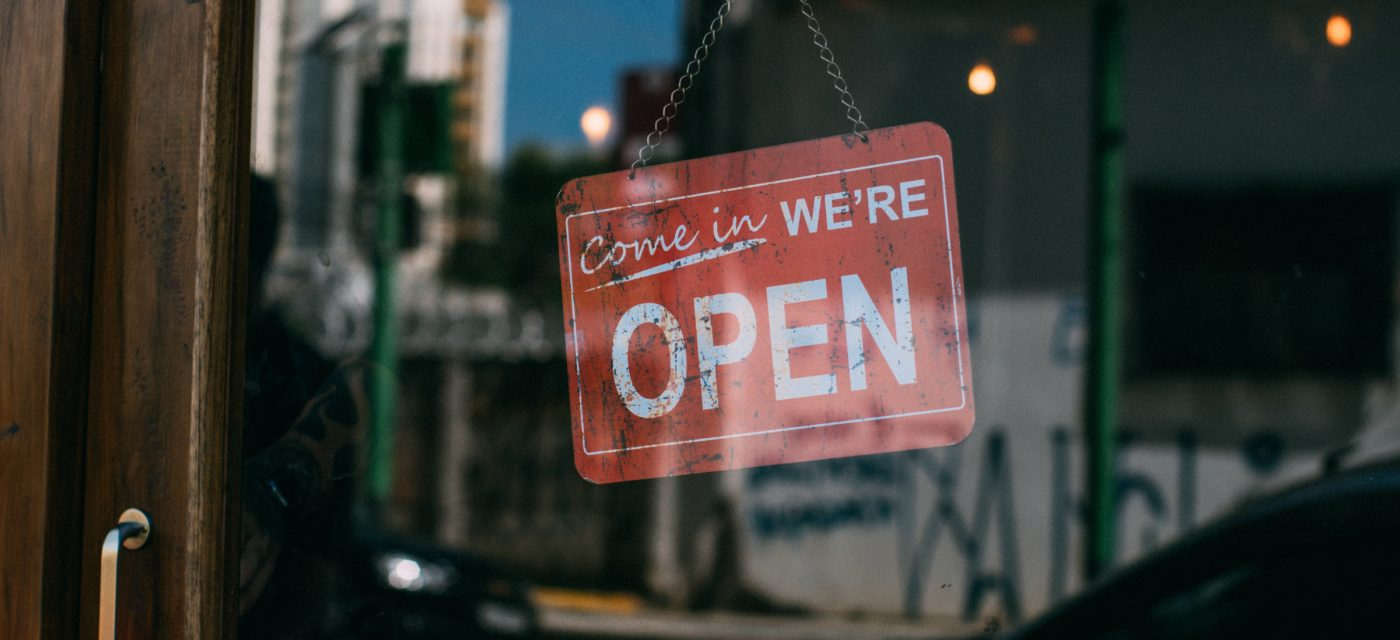 """A sign that reads, """"Come In We're Open"""" is hanging on the inside of a glass door and is being viewed from outside."""