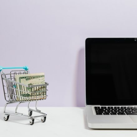 A tiny shopping cart filled with cash sits next to a laptop.