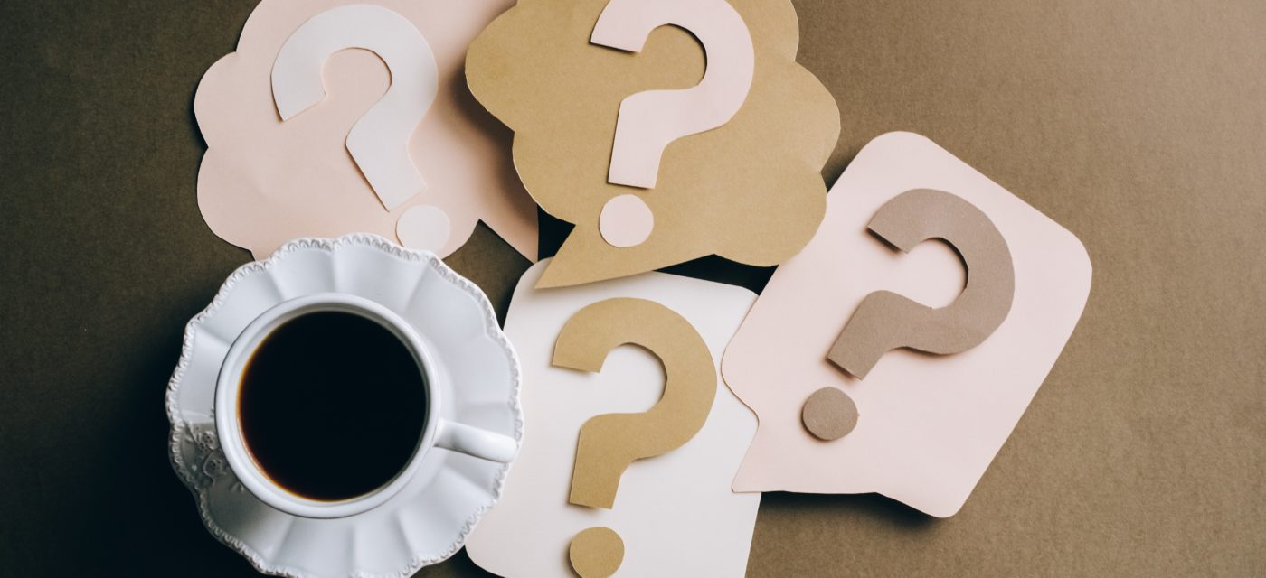 A cup of coffee on a table along with papercraft question marks