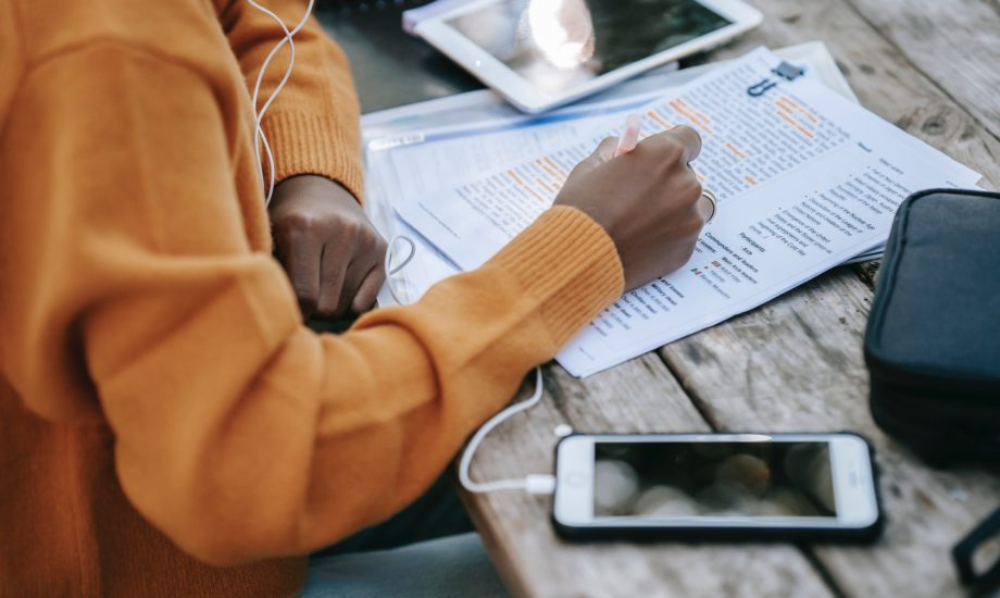 A black woman in an orange sweater is highlighting text on a printed piece of paper. To her right is a smartphone with a cord for headphone going towards her head. On her left is a tablet computer.