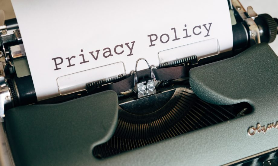 """An old manual typewriter is shown with a piece of paper on which the words """"Privacy Policy"""" have been typed."""