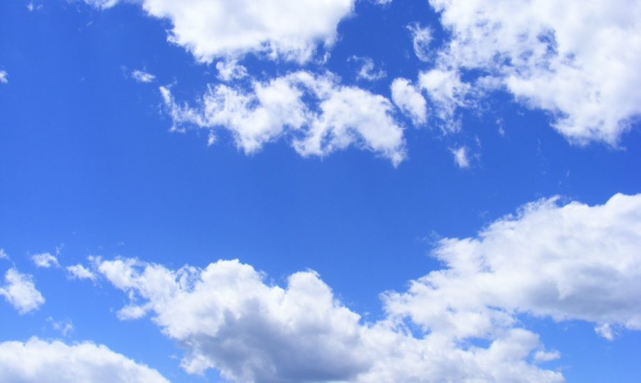 A bright blue sky with several fluffy white clouds