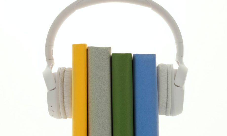A pair of white wireless headphones is mounted on four books with different colored spines.