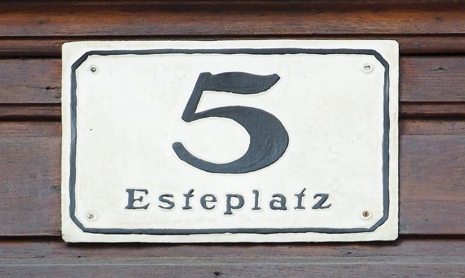 A black painted numeral 5 on a white plaque screwed to a wooden board