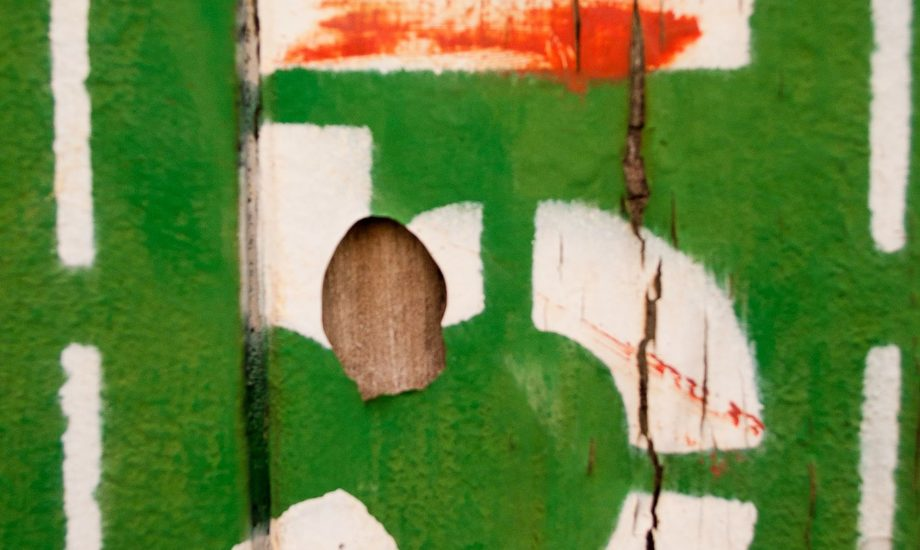 A stenciled white number five painted on a green wooden board