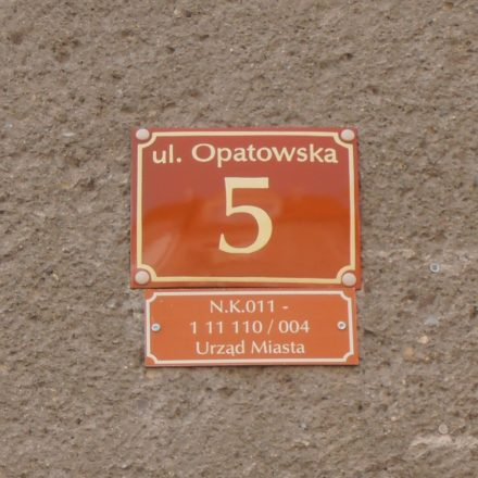 A yellow numeral 5 painted on a brown plaque that has been nailed to a stucco wall