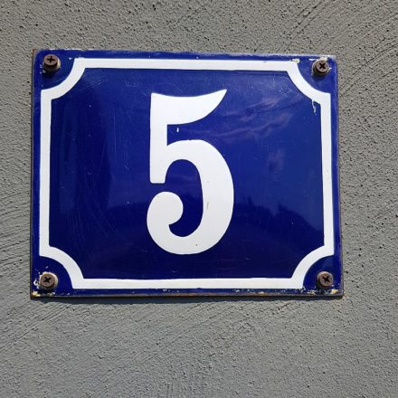 A white numeral 5 on a blue painted metal sign that has been screwed to a wall