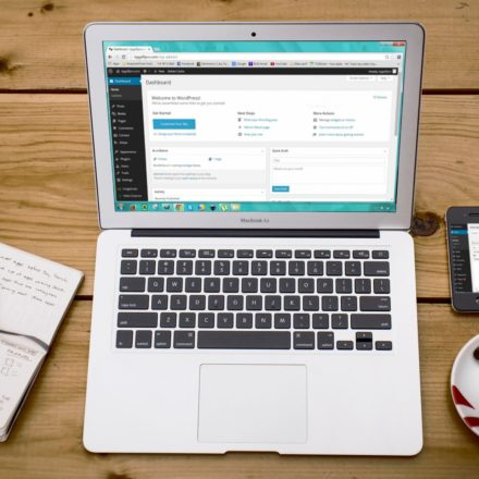 A photo of a laptop displaying the Dashboard of a WordPress Blog. The laptop is on a wooden table. To the left of the laptop is a notebook and a pen, while to the right of the laptop are a smartphone and a cup of espresso.