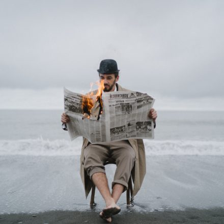 A photo of a man in a tan trenchcoat and a black bowler hat sits on a chair on a beach, and is holding a newspaper open and it turns to flame.