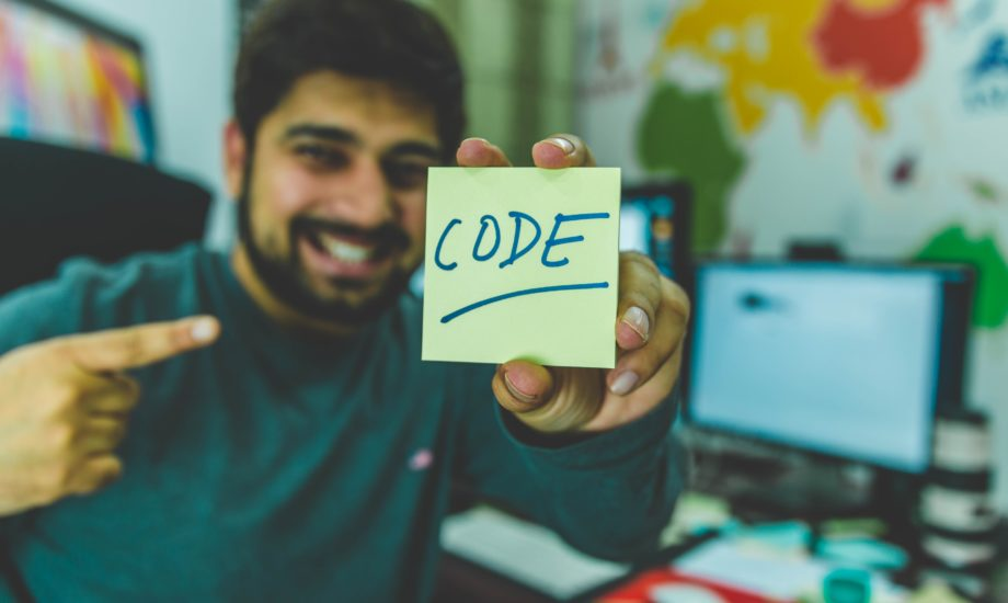 A bearded man in a grey sweater is holding a yellow sticky note which has CODE written upon it.