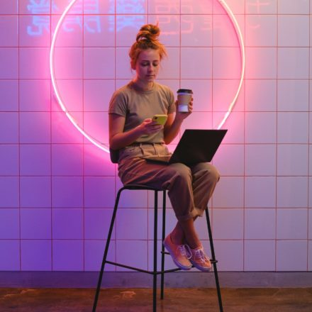 A photo of a woman sitting on a stool in front of a white tiled wall. A large neon circle is hanging on the wall and neon chinese characters are reflected in the glaze of the tiles. The woman is holding a coffee cup in one hand, a smartphone in the other, and has a laptop on her lap.